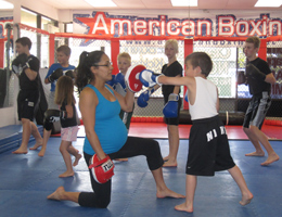 Coach Gina holds mitts for kids boxing class while pregnant.